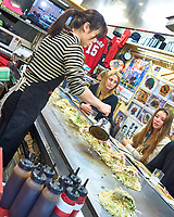Okonomiyaki, a traditional Japanese savory pancake being cooked on a grill in Hiroshima. Image taken with a Leica T camera and 23 mm f/2 lens.