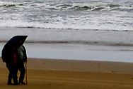 An elder couple out during a storm on the Oregon coast with an umbrella and a cane.