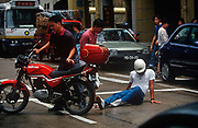 While still a Portuguese colony, a 1990s Macau motorbike rider picks himself up after a road traffic collision, on 10th August 1994, in Macau, China.