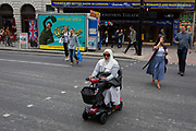 A Muslim lady wearing her hijab rides on her mobile scooter, crossing opposite the Dominion Theatre on Tottenham Court Road  on 10th August 2017, in London, England.