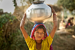 Kotha Bai's daughter Rekha gets water from a well in the village of Purumpur in Rajasthan October 26, 2010. Kotha Bai will be giving testimony at a tribunal in Delhi to talk about the changes in climate in the last few decades. She says the span of summer has increased while the winter and rains have decreased, forcing many people to leave the village in search of a better life in the cities.