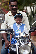 A man and his schoolgirl daughter in a French uniform wait on their motorcycle for school to open, Pondicherry, India. Pondicherry now Puducherry is a Union Territory of India and was a French territory until 1954 legally on 16 August 1962. The French Quarter of the town retains a strong French influence in terms of architecture and culture.