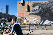 Cyclists ride through graffiti's streets in Shoreditch, London<br /> Shoreditch, an area that was dominated by light industry is now home to creatives and the streets are decorated with a good deal of graffiti - much by established street artists