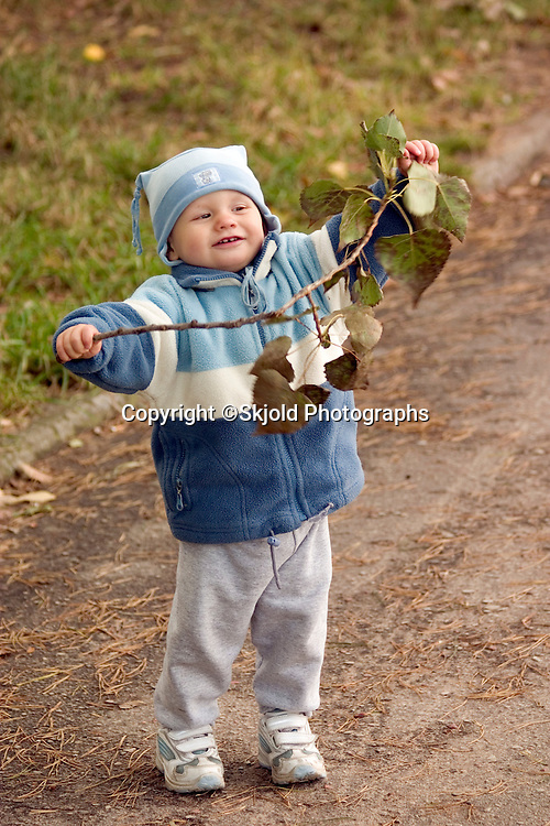 Happy Polish toddler holding a branch of leaves. Rawa Mazowiecka Central Poland