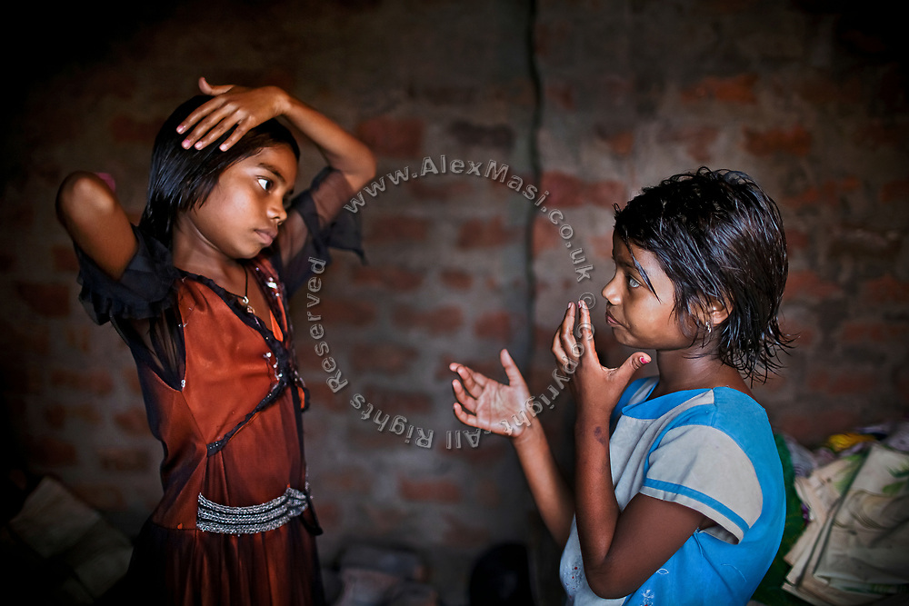 Jyoti, 10, (left) and her younger sister Poonam, 9, (right) are oiling their hair while getting ready for school, as they stand inside their newly built home in Oriya Basti, one of the water-contaminated colonies in Bhopal, central India, near the abandoned Union Carbide (now DOW Chemical) industrial complex, site of the infamous '1984 Gas Disaster'.
