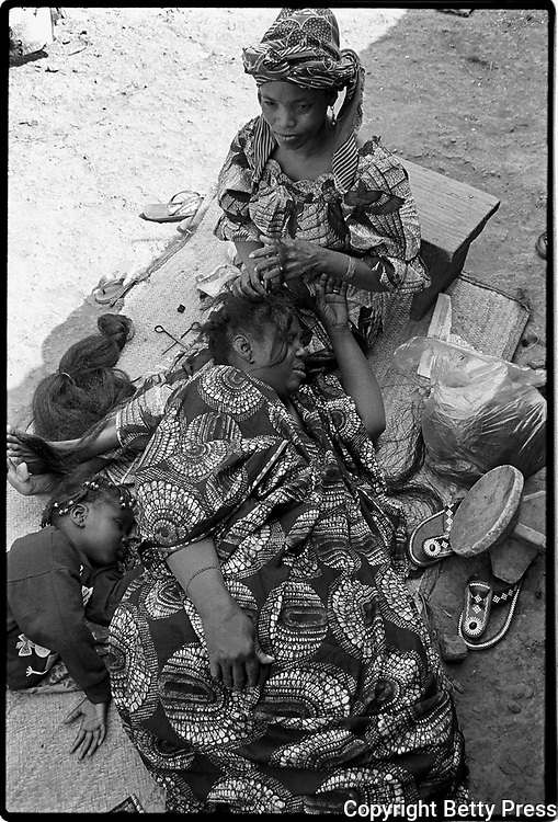 The wise do not comb themselves; if they do, they get hurt.  Ugandan proverb <br /> <br /> A woman is having her hair styled.  As it will take several hours she makes herself comfortable, along with her daughter.  Women in Mali have a sophisticated sense of fashion, particularly in terms of their clothes and hairstyles.  The cheapest place to have their hair done is in the open-air market where a large, covered shed is devoted to this trade. Bamako, Mali  1992