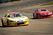 Charlie Imus in the yellow number twenty Impala, left, passes around some competition during his ten lap race on the Stateline Speedway Sunday afternoon.
