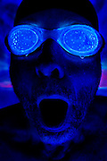 A male swimmer with glowing goggles takes a huge breath of air.Black light