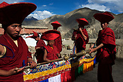 Dharma trumpets are blown during festivities. Monks and pilgrims mix to celebrate the Lamayuru Festival 5-6 June, 2013, Lamayuru Monastery. Lamayuru Gompa (monastery) is built above the ruins of the old one, along the Srinagar-Leh highway.