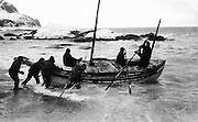 """The James Caird lifeboat is launched from the shore of Elephant Island in the South Shetland Islands on 24 April 1916. This photograph, probably captured by expedition photographer Frank Hurley, was published in the United States in Ernest Shackleton's 1919 book, """"South,"""" from William Heinemann publishing house of London. The voyage of the James Caird, one of history's greatest small-boat journeys, was by open whaleboat from Elephant Island to South Georgia in the southern Atlantic Ocean, a distance of 800 nautical miles (1500 km; 920 mi) across one of the world' s most treacherous seas. Undertaken by expedition leader Sir Ernest Shackleton and five companions, its objective was to obtain rescue for the main body of the Imperial Trans-Antarctic Expedition of 1914-17, trapped on Elephant Island after the loss of their ship Endurance. On the temporary haven of Elephant Island, the expedition's carpenter, Harry McNish, improvised tools and materials to adapt the 22.5-foot (6.9 m) long James Caird, raising its sides and building a makeshift deck of wood and canvas, sealing the work with oil paints, lamp wick, and seal blood. The craft was further strengthened with a mast lashed inside along the length of her keel, and fitted with a mainmast and a mizzenmast, rigged to carry lugsails and a jib. Boat weight was increased by 1 long ton (1016 kg) of ballast, to lessen the risk of capsizing in the high seas that Shackleton knew would be encountered. (This photo is in the public domain in the United States because its first publication occurred prior to January 1, 1923.)"""