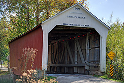 06 October 2013: The Phillips Covered Bridge crosses Big Pond Creek on County Road South 420 West at County Road West 40 North southeast of Montezuma in Parke County. This single span Multiple King Post Truss structure has a length of 43 feet, or 61 feet including the 9-foot overhang at each end, is 16 feet wide and 14 feet high. Built in 1909 by Joseph A. Britton, though no historical marker is present, it was listed on the National Register of Historic Places in 1978.<br />