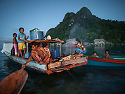 Cooking diner of coral fish, over a fire. Bajau family living all year round on a Lepa, a traditional houseboat.