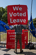 A man holds a huge sign with the words We Voted Leave outside Westminser on the 23rd July 2019 in London in the United Kingdom.