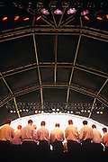 Seen low from behind stage, a male voice choir are lined up to sing during their performance at an open-air temporary auditorium during the Lambeth Show, an inner-city cultural and family event held annually in Dulwich Park, a leafy suburb of South London. The choristers are dressed in white shirts which are untidily untucked from their dark trousers (pants). Their heads echo the purple, yellow and red spots from the overhead lights. The front of stage is covered by a curved ribbed roof structure that arches over the mens' heads. The singers look small in scale to the cavernous height of this ceiling, occupying a small percentage of the frame. We cannot see the choir's conductor, nor their audience but we get an impression of wide area in which to project their voices