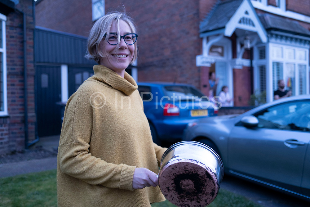Local resident in Moseley bangs a cooking pot as she takes part in the weekly Clap for Carers response to Coronavirus in support of NHS staff and key-workers on 9th April 2020 in Birmingham, England, United Kingdom. Coronavirus or Covid-19 is a new respiratory illness that has not previously been seen in humans. While much or Europe has been placed into lockdown, the UK government has announced more stringent rules as part of their long term strategy, and in particular social distancing.