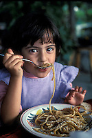 girl eating Bucatini with rabbit, in Ischia, near Naples - Photograph by Owen Franken