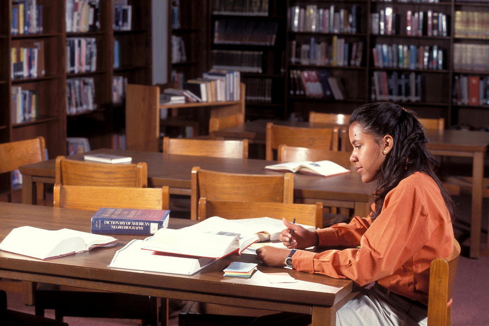 African-American high school female doing research in Library.<br /> ©Bob Daemmrich/