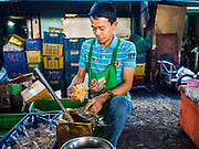 30 DECEMBER 2015 - BANGKOK, THAILAND:  A vendor packages palm sugar in Bang Chak Market. The market is supposed to close permanently on Dec 31, 2015. The Bang Chak Market serves the community around Sois 91-97 on Sukhumvit Road in the Bangkok suburbs. About half of the market has been torn down. Bangkok city authorities put up notices in late November that the market would be closed by January 1, 2016 and redevelopment would start shortly after that. Market vendors said condominiums are being built on the land.           PHOTO BY JACK KURTZ