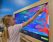 """Adilyn Ruge, 10, uses a regular paintbrush on the """"electronic easel"""" touch-sensitive monitor to paint a digital picture. Children can email the finished artwork from the Magic House. It's one of the more popular interactive exhibits at the new site. The Magic House had two fourth-grade classes from the New City School visit their new permanent satellite location at 5127 Delmar Boulevard in St. Louis, MO on Wednesday May 23, 2019.<br /> Photo by Tim Vizer"""