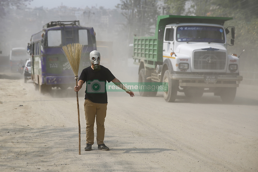 May 7, 2017 - Kathmandu, Nepal - Artist Milan Rai wearing a gas mask stages a performance art protest against the pollution on a polluted road in Kathmandu, Nepal on Sunday, May 07, 2017. Kathmandu ranks among the world's most polluted cities in the world. (Credit Image: © Skanda Gautam via ZUMA Wire)