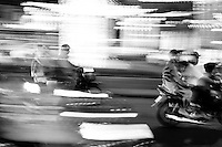 Motorbikes whizz by on the streets of Saigon in a blur of colour and light.