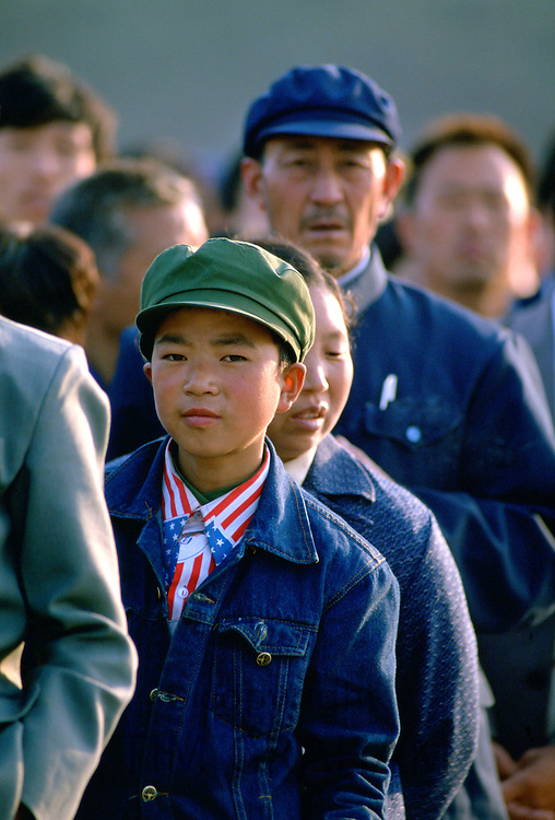 Chinese boy wearing a patriotic American stars and stripes shirt and denim jacket queues to enter the Great Hall of the People  in Tiananmen Square, Beijing, China