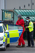 """Tamworth, United Kingdom, May 25, 2021: Police handcuffed and accompany one of three arrested activists of the """"Palestine Action"""" activist group who scaled on the rooftop of an Israeli owned arms manufacturer Elbit on the early morning of Tuesday, May 25, 2021. Activists painted red colour on Building's roof as well as its logo """"Elite KL"""".  (Photo by Vudi Xhymshiti)"""
