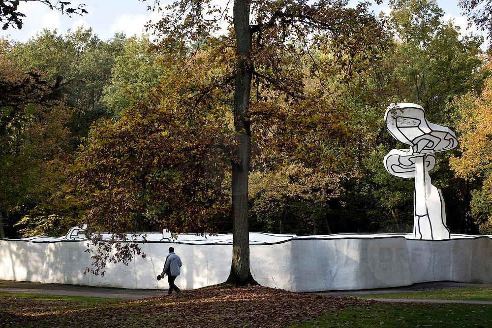 Nederland Otterlo 29 oktober 2008 20081029 Foto: David Rozing ..Herft tafereel, man loopt langs Jardin d'email van Jean Dubuffet in de beeldentuin van het Kröller-Müller Museum. Op de voorgrond een boom in herfstkleuren, op de achtergrond een boom als kunststuk van de  Jardin d'email.Het museum ligt midden in het Nationale Park de Hoge Veluwe..Fall in The Netherlands, a man takes a stroll in National Park de Hoge Veluwe, in the garden of the Kroller Muller museum. In the background is the object of art  Jardin d'email, by Jean Dubuffet..Foto: David Rozing