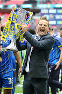 Neal Ardley, the AFC Wimbledon manager celebrates as he lifts the Sky Bet League 2 Play-off Trophy. Skybet football league two play off final match, AFC Wimbledon v Plymouth Argyle at Wembley Stadium in London on Monday 30th May 2016.<br /> pic by John Patrick Fletcher, Andrew Orchard sports photography.