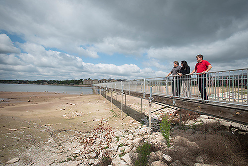 Granbury, Texas resident Joe Williams, right, stands with city councilwoman Rose Myers and Hood County Commissioner Steve F. Berry on a Lake Granbury walkway that overlooks the ever-receding lake near the public swimming area. The lake is 10 feet below normal levels.