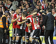 Brentford players celebrate Brentford's Stuart Dallas winner during the Sky Bet Championship match between Brentford and Derby County at Griffin Park, London, England on 1 November 2014.