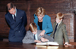 Prince William signs the traditional Entrance Book watched by his parents, the Prince and Princess of Wales, and younger brother, Prince Harry, at Eton College.