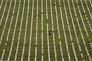A person kneels next to a tombstone during Memorial Day at the Golden Gate National Cemetery in San Bruno, Calif., Monday, May 29, 2017.