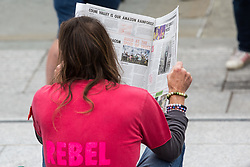 London, UK. 23rd August, 2021. An environmental activist from Extinction Rebellion reads a spoof newspaper in Trafalgar Square during the first day of Impossible Rebellion protests. Extinction Rebellion are calling on the UK government to cease all new fossil fuel investment with immediate effect. Credit: Mark Kerrison/Alamy Live News