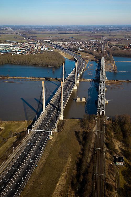 Nederland, Gelderland, Zaltbommel, 07-03-2010; bruggen over de rivier de Waal, gezien naar de Tielerwaardwaard met Waardenburg in de achtergrond Rechts de spoorburg (spoorlijn Utrecht - Den Bosch), links de Martinus Nijhofbrug (rijksweg A2 richting Utrecht, aan de horizon). De oude brug voor autoverkeer is gesloopt (pijler nog in de rivier)..Bridges over the River Waal, in the direction of the Tilerwaard. Right the railway bridge (railway line Utrecht - Den Bosch), left the Martinus Nijhof bridge right (A2). The old traffic bridge has been demolished (pillar still in the river)..luchtfoto (toeslag), aerial photo (additional fee required).foto/photo Siebe Swart