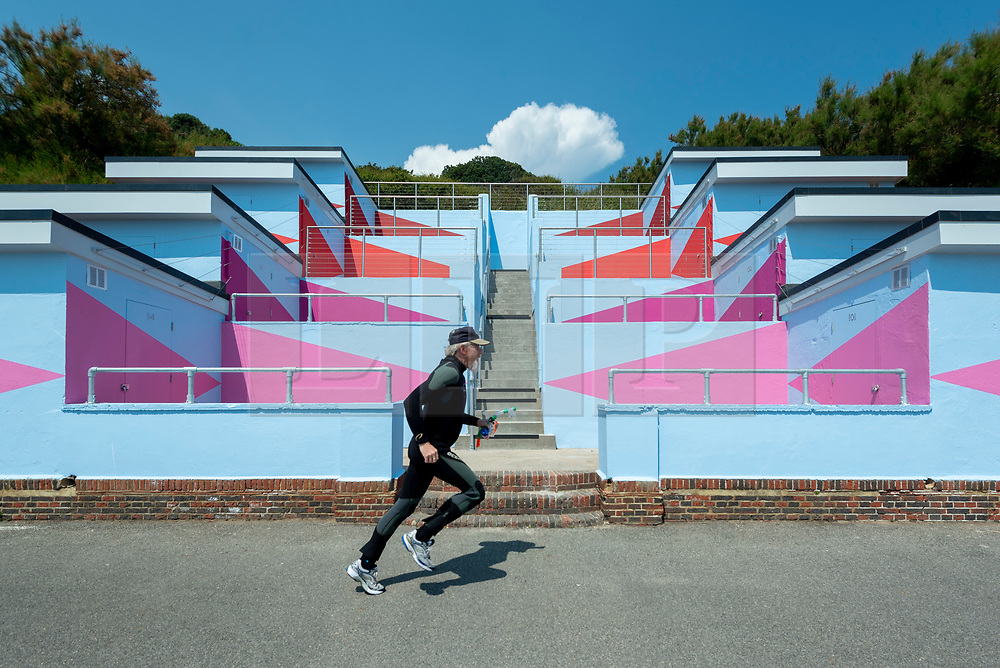"""© Licensed to London News Pictures. 20/07/2021. FOLKESTONE, UK. """"No 1054 Arpeggio"""", 2021, by Rana Begum - a special colour scheme to 120 beach huts. Preview of The Plot exhibition, the fifth Creative Folkestone Triennial. Folkestone has no publicly subsidised art gallery, so artists were invited to use public spaces to create new artworks in the seaside town. Over 20 works by artists including Assemble, Rana Begum, Gilbert & George, Atta Kwami, Pilar Quinteros, and Richard Deacon are on display 22 July to 2 November 2021.  Photo credit: Stephen Chung/LNP"""