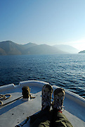 Feet of passenger on bow of boat, island of Korcula in background.
