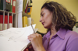 Young woman looking through file in school office,