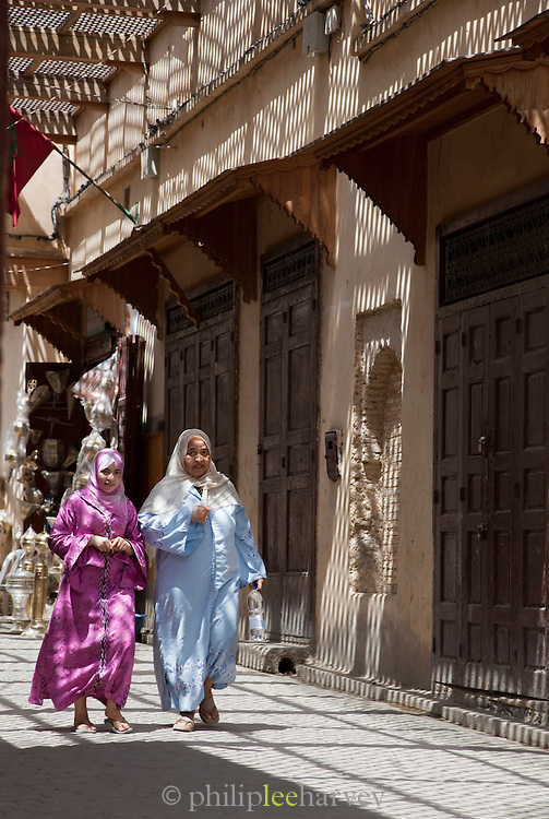 Women walk through the narrow streets of the medina in Fes, Morocco
