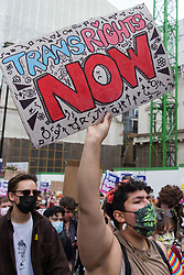 A protester holds a sign reading Trans Rights Now as thousands of people take part in a London Trans+ Pride march from the Wellington Arch to Soho Square on 26th June 2021 in London, United Kingdom. London Trans+ Pride is a grassroots protest event which is not affiliated with Pride in London and focuses on creating a space for the London trans, non-binary, intersex and GNC community to come together to celebrate their identities and to fight for their rights.