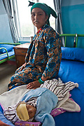 A very sick Nepalese baby lies on a hospital bed and his concerned mother sits next to him on a ward in the Friends of Needy Children Nutritional Rehabilitation Centre, Kathmandu, Nepal.  The child is 8 months old, but extremely small due to chronic malnutrition.  He arrived in the centre 4 days ago and weighed 3.1kg.  He is undergoing an intensive nutrition program and has already gained 0.6kg.  Malnutrition prevents normal  growth and development.
