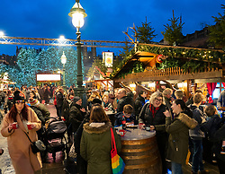 View of people eating and drinking at stalls in busy Edinburgh Christmas Market in West Princes Street gardens in Edinburgh, Scotland, UK