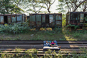 Two children laying on bed mattress on train tracks, old abandoned station, train cars and steel, Mawlamyine