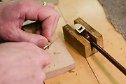 Beekman cutting a wedge to hold the horsehair into a bow's tip.