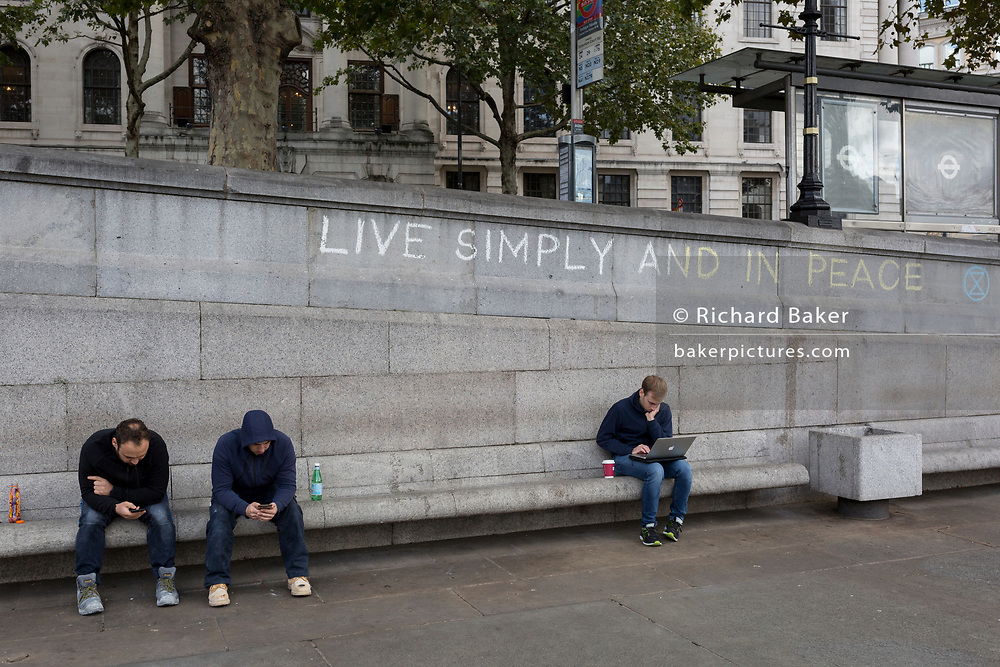 Three men use their phones and a laptop beneath the slogan 'Live Simply and Live in Peace' has been written on a wall by an environmental activist protesting about Climate Change during an occupation of Trafalgar Square in central London, the third day of a two-week prolonged worldwide protest by members of Extinction Rebellion, on 9th October 2019, in London, England.