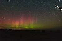 The northern lights dance above Deadman's Basin Reservoir while a fireball meteor flies through the sky.