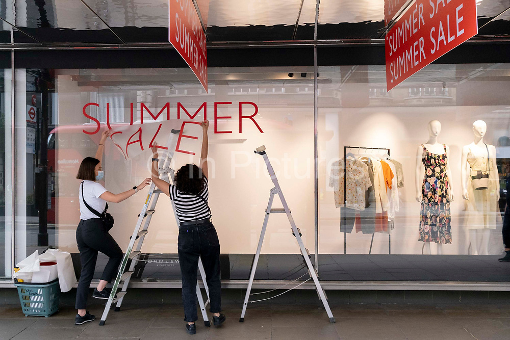 Staff from High Street retailer John Lewis attach sticky transfers for the upcoming John Lewis Summer Sale on Oxford Street, on 5th July 2021, in London, England.