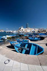 Barche in secca nella darsena del porto di Gallipoli (LE), sullo sfondo sono visibili la chiesa del Canneto e il grattacielo.