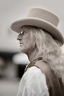 Platinum emulsion portrait in profile of a man with long wavy blond hair wearing wire rim glasses, a top hat, vest and white long sleeve shirt.