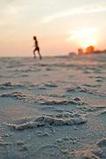 A girl takes a run across the beach at sunset.
